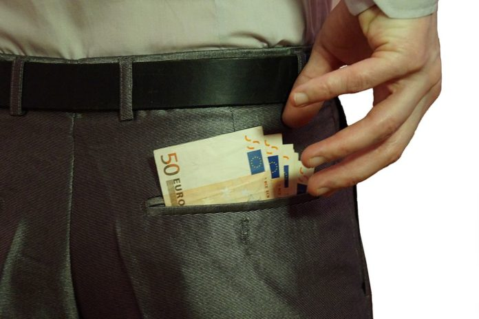 Teachers pay out of pocket. Man reaching to his back pocket for euro notes.